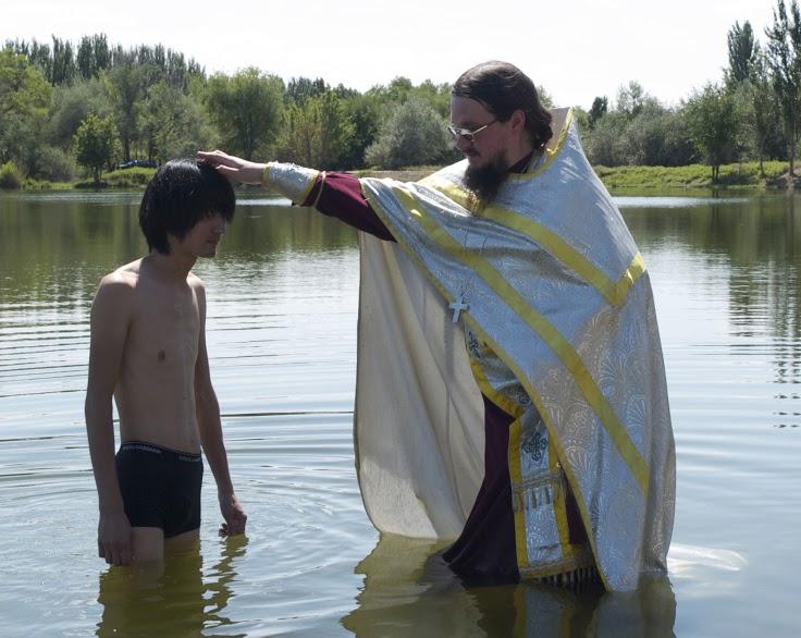 Le père Daniel célébrant le baptême